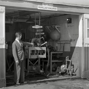 Man pointing to rocket engine in test cell.