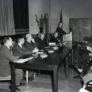 Men seated at table.