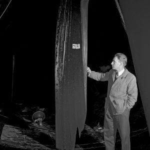 Man examines damaged wooden fan blade .