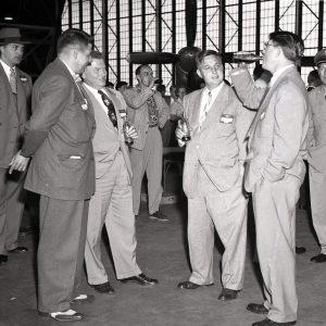 Men drinking Cokes in hangar.