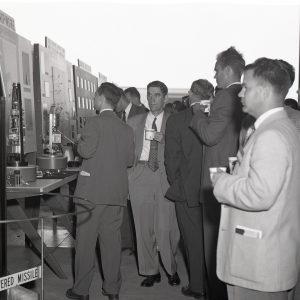 Men talking in hangar.