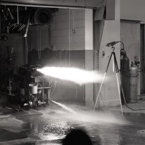 Firing of a rocket engine in Cell 21 of the Rocket Lab. A camera is set up to record the test.