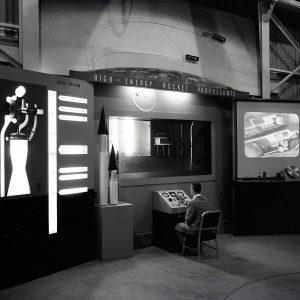 Man seated at control panel at RETF display.
