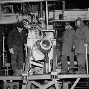Three men on with rocket engine on platform in J-1
