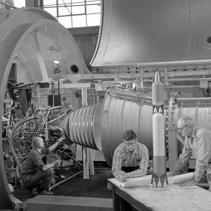 John Kobak and an engineer examine a drawing and model of the Atlas/Centaur while a technician inspects the setup of a Pratt & Whitney RL-10 rocket engine in a PSL test chamber.