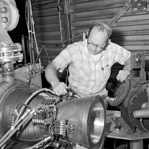 A technician inspects an experimental copper nozzle at the J-1 test rig
