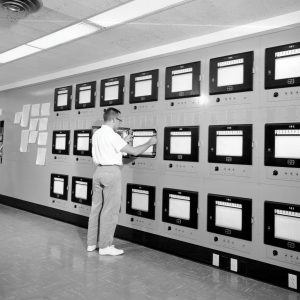 Operators watch chart recorders on wall in H Control