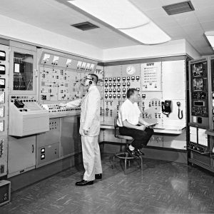 Two men at control panels in H Control Building