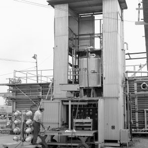 A technician inspects the installation of an experimental arc tank at the J-4 vertical test stand