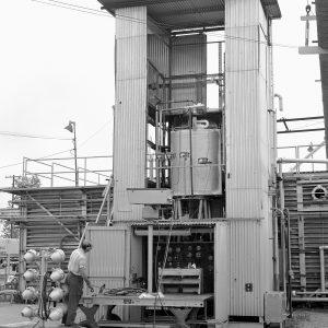 A technician inspects the installation of an experimental arc-shaped tank at J Site's J-4 vertical test stand