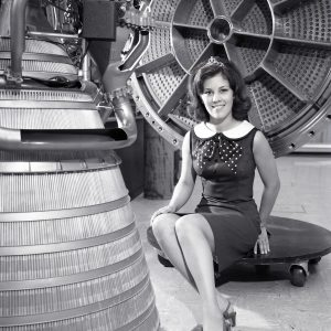 Woman poses with rocket engine.