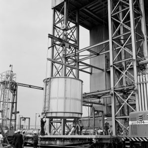 Ground-level view of crane lifting test article into B-3