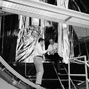 Two researchers examine cryoshroud in open K Site chamber