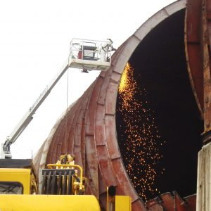 Man in lift with torch cutting tunnel shell.