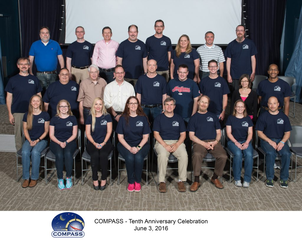 Compass team members posed for a group photo in three lines, wearing largely matching team shirts.