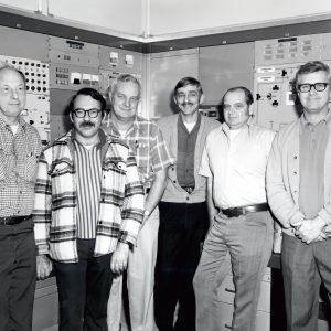 FIve men posing in control room.
