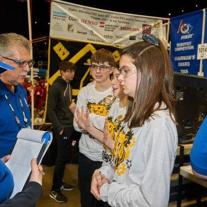 A boy and a girl from team 6964 being interviewed by two Buckeye Regional judges.