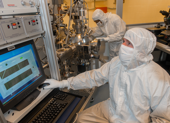 Workers in white protective suits running equipment in the NASA Glenn Class 100 clean room.