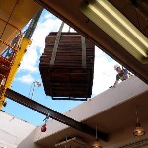 Crane lifting load through roof.