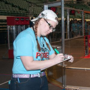 A volunteer queuer helps robots be in the right place prior to them competing on the field.