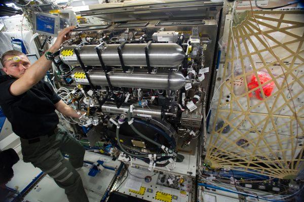 NASA astronaut Reid Wiseman, Expedition 40 flight engineer, sets up the Combustion Integrated Rack (CIR).